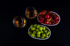 Single malt tasting glasses, single malt whisky in a glass, whit. E and red grapes in white bowls, black background royalty free stock photo