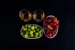Single malt tasting glasses, single malt whisky in a glass, whit. E and red grapes in white bowls, black background royalty free stock images