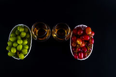 Single malt tasting glasses, single malt whisky in a glass, whit. E and red grapes in white bowls, black background royalty free stock photography