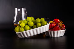 Single malt tasting glasses, single malt whisky in a glass, whit. E and red grapes in white bowls, black background royalty free stock photos