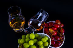 Single malt tasting glasses, single malt whisky in a glass, whit. E and red grapes in white bowls, black background stock image