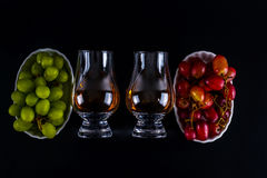 Single malt tasting glasses, single malt whisky in a glass, whit. E and red grapes in white bowls, black background royalty free stock image