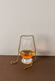 A single malt whiskey glass, on a brown plane, with a gold chain Royalty Free Stock Images