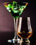 Single malt whiskey in a glass and green mint liqueur, refreshin. G set of drinks, taste sensations Royalty Free Stock Images