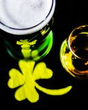 Single malt whiskey in a glass of tasting with decoration for St. Patrick`s day, green clover symbol for Irish holiday, festive Royalty Free Stock Photography