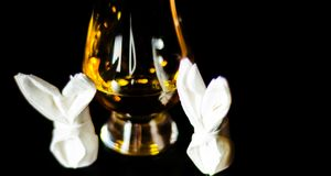 Single malt whiskey in a glass of tasting with napkin bunny, fes. Tive Easter decoration, holiday Stock Photos
