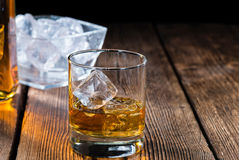 Single Malt Whiskey. With Ice Cubes on wooden background Royalty Free Stock Photo