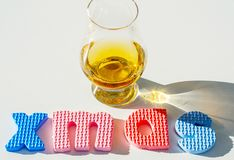 Single malt whisky in the glass with rubber letters, xmas inscr. Iption, luxurious tasting glass, drink set royalty free stock photos