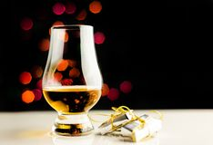 Single malt whisky in tasting glass on christmas background, co. Lorful bokeh, xmas time royalty free stock photos