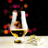 Single malt whisky in tasting glass on christmas background, co. Lorful bokeh, xmas time royalty free stock photography