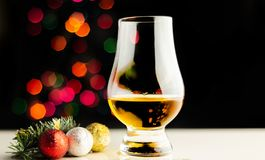 Single malt whisky in tasting glass on christmas background, co. Lorful bokeh, xmas time stock images