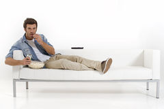 Single man on the couch watching TV. Eating pop corn Royalty Free Stock Photos