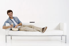 Single man on the couch watching TV Royalty Free Stock Photography