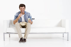 Single man on the couch watching TV. Eating pop corn Stock Photography