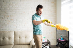 Handsome Latin man dusting his house. Single man dusting his furniture to keep the dust away from them and have a clean house stock photos
