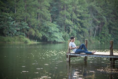Single man listen music on dock. In lake at Pang-ung, Mae Hong Son, North of Thailand stock photos