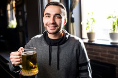 Single man in a pub or bar holding mug the beer high in the air for cheers Royalty Free Stock Photos