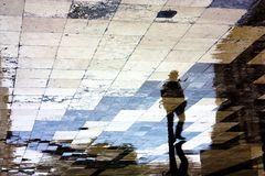 Single man reflection silhouette on wet sidewalk stock images