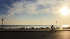 Single man riding bicycle near the sea in morning ; Songkhla province, Thailand. Silhouette style Stock Image