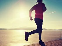 Single man running workout, excercise for run near frozen lake. Single man running workout, excercise for  run near frozen lake. Training and working out, runner stock photo