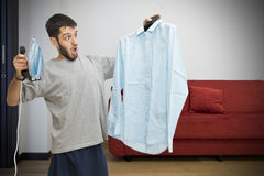 Single man scared about ironing Royalty Free Stock Photo