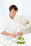 Single man serving salad standing at a table Stock Photos