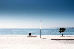 Single man sitting on a bench and looking at the sea. Lonely sad Stock Images