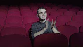Single man sitting in comfortable red chairs in dark cinema theater and applauds.  stock video footage