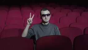 Single man sitting in comfortable red chairs in dark cinema theater and doing victory sign with fingers. Smiling satisfied to the camera stock video