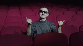 Single man sitting in comfortable red chairs in dark cinema theater and inviting to join.  stock footage