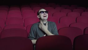 Single man sitting in comfortable red chairs in dark cinema theater and laughs. Handsome man watching comedy stock video