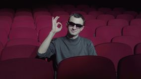 Single man sitting in comfortable red chairs in dark cinema theater and showing ok sign.  stock footage