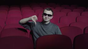 Single man sitting in comfortable red chairs in dark cinema theater and showing thumbs down. Dislike concept stock video