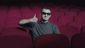 Single man sitting in comfortable red chairs in dark cinema theater and showing thumbs up. Young man liked film, recommends performance stock footage