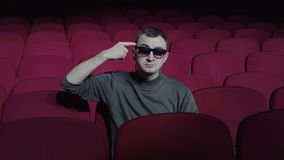 Single man sitting in comfortable red chairs in dark cinema theater and twists her finger at her temple.  stock video