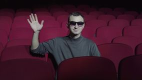 Single man sitting in comfortable red chairs in dark cinema theater and waving hand to camera.  stock video footage