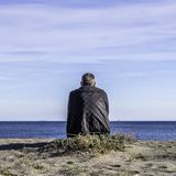 A single man sitting on an empty beach looking out to sea and blue sky with white clouds royalty free stock photo