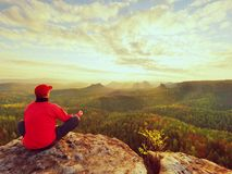 Single man tourist  sit on rock empire. View point with exposed rocky peak above valley. Stock Images