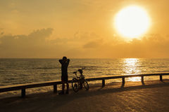 Single man warm down after riding bicycle in the park near the sea in morning ; Songkhla province, Thailand. Silhouette style royalty free stock photos