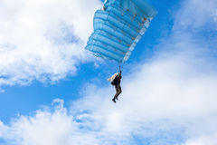 Single military parachute jumper on a blue wing parachute Royalty Free Stock Photo