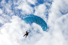 Single military parachute jumper on a blue wing parachute Stock Photo