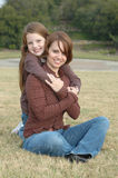 Single Mom. Beautiful little girl hugging her mother in a park setting Stock Images