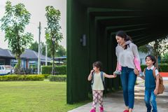 Single mom carrying and playing with her children in garden with green wall background. People and Lifestyles concept. Happy royalty free stock photo