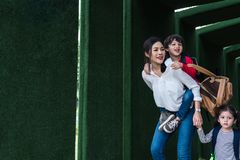Single mom carrying and playing with her children in garden with green wall background. People and Lifestyles concept. Happy stock images