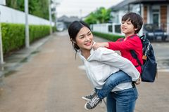 Single mom carrying and playing with her children near home with. Villa street background. People and Lifestyles concept. Happy family and Home sweet home theme stock photo