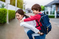 Single mom carrying and playing with her children near home with villa street background. People and Lifestyles concept. Happy. Family and Home sweet home theme royalty free stock photo