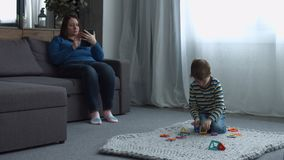 Single mom and cute son enjoying leisure at home stock video