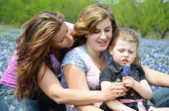 Single Mom with Daughters. Single mom with her two daughters holding a bluebonnet flower stock images