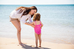 Single mom enjoying the beach. Portrait of a beautiful young single mother spending the day at the beach with her daughter stock image