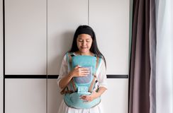 Single mom felling happy with her baby in a baby carrier. Single asian mom felling happy with her baby in a baby carrier royalty free stock photo
